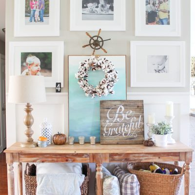 A cozy console table and gallery wall decked out for fall in simple, turquoise and wood toned elements