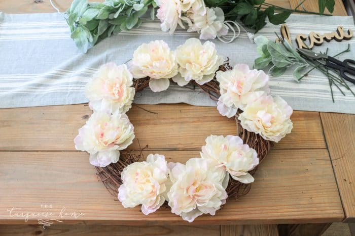 Add the peonies first to the lamb's ear wreath.