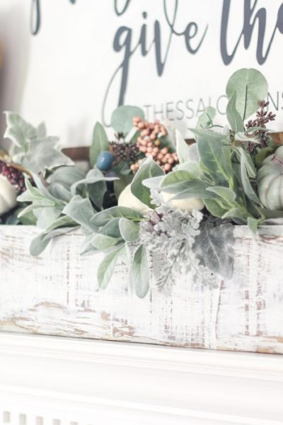 Adorable faux foliage centerpiece made with a wooden box, mason jars and faux stems. LOVE!