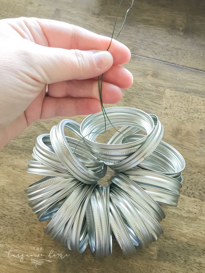 String the adorable mason jar lid pumpkins on a wire string and voila! Cutest pumpkin you ever did see! Click here for the full tutorial...