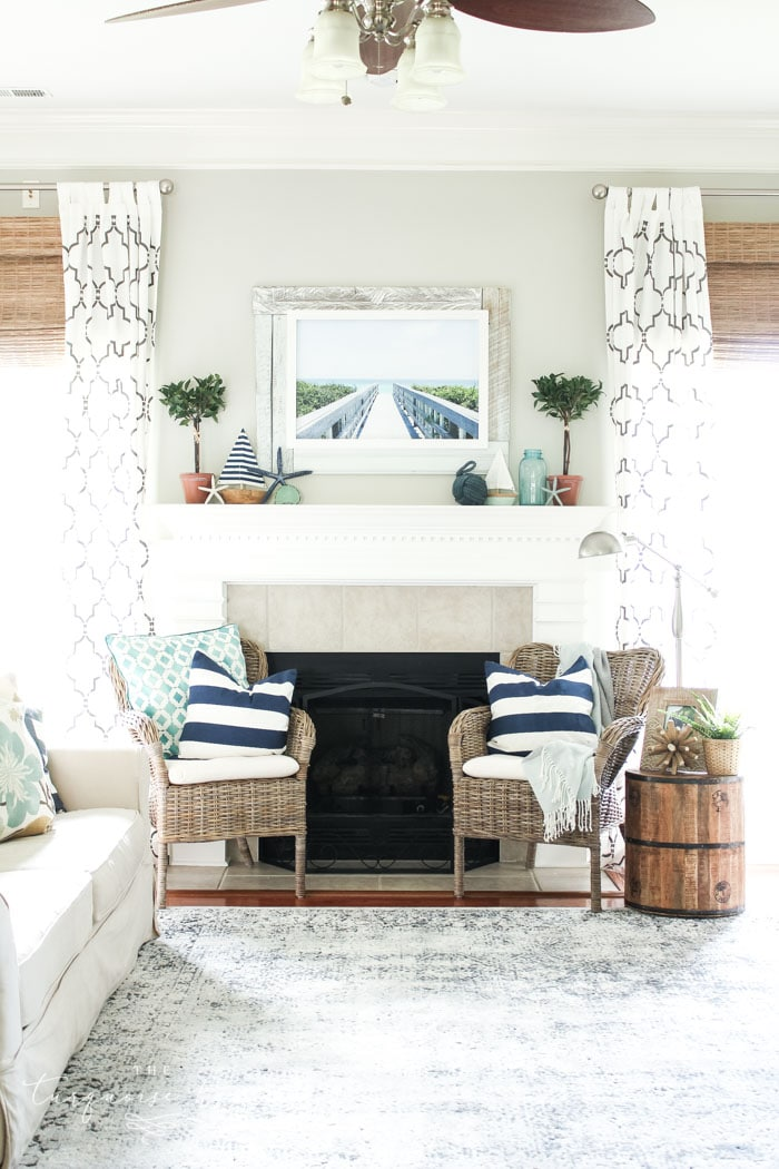 Add a little nautical charm to your living space with these simple coastal summer mantel decor ideas. Featuring DIY beach canvas art, blue & white starfish, textured sailor's knot and cheerfully striped sail boats, this mantel looks great for the seasonally inspired.