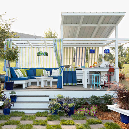 This space boasts an outdoor kitchen, sitting area, outdoor checkerboard, and colorful finishing touches, including outdoor fabrics that add color and style.