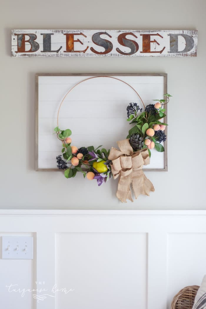 "Gorgeous fall wreath with fruit on a ""shiplap"" framed backdrop."