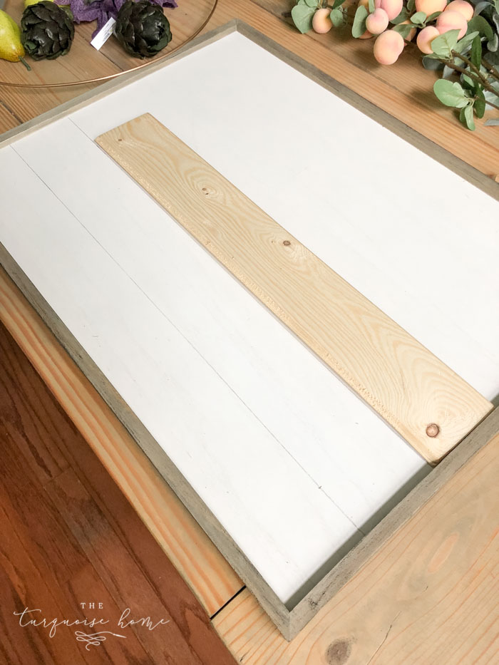 "Draw ""shiplap"" lines on the framed board with a pencil and a scrap piece of wood!"