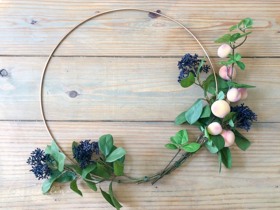 Attach the floral and fruit stems to the wreath hoop.