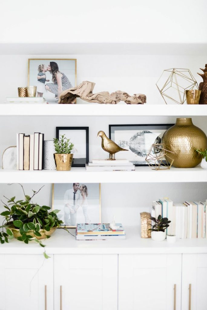 How to Style a Bookshelf -->> White shelving styled with gold sculpture and books