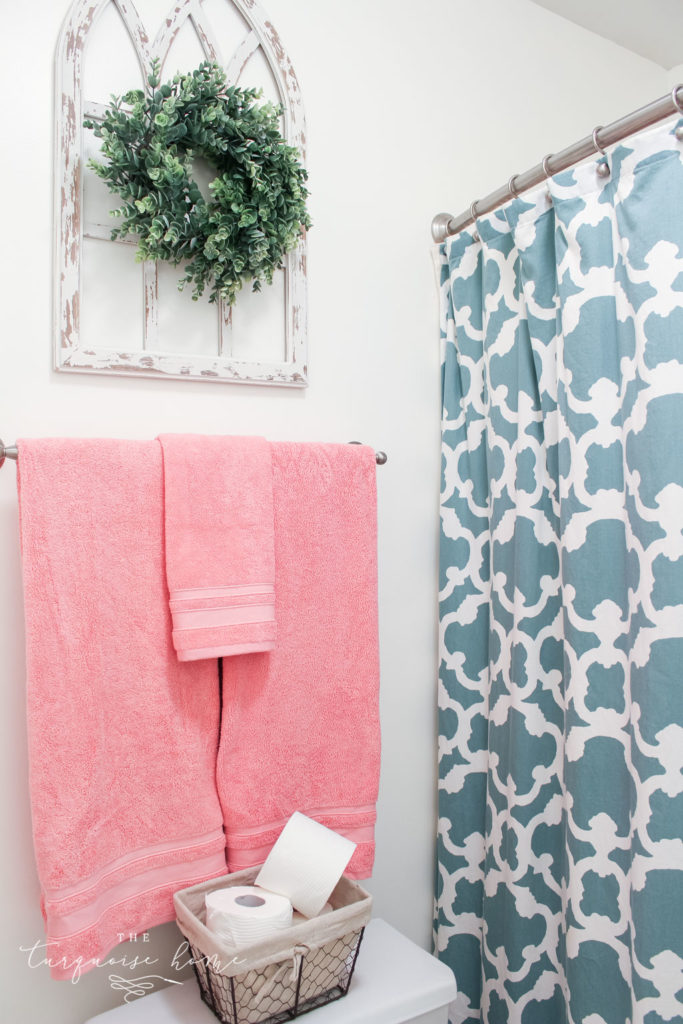 Window arch above the toilet in the girls' bathroom refresh | Use a basket for toilet paper storage and a over-the-toilet cabinet if needed | bathroom makeover | pink towels | antique distressed window frame | eucalyptus wreath