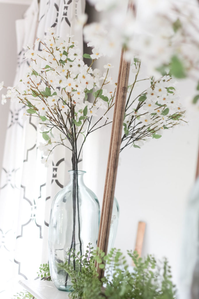 A Simple Summer Mantel -->> wood mirror, glass vase, dogwood stems and locust garland