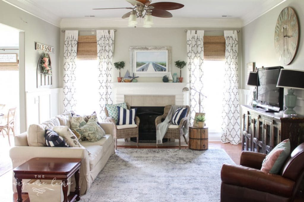 living room that uses home and decor to create a comfortable space with a sofa and two chairs in front of a fireplace.