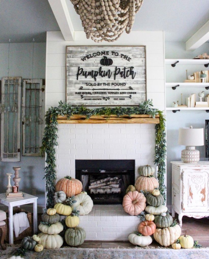 Gorgeous fall decor that can transition into Halloween with stacks of pumpkins all over the fireplace hearth!