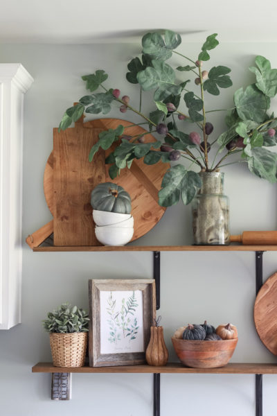 Open kitchen shelves decorated for fall   fig leaves   fiddle leaf fig   cutting boards   antique pizza boards   fall decor ideas