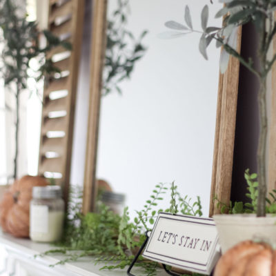 "Shutter and olive tree with ""let's stay home"" sign and a wood grain pumpkin. Fall Mantel Decor #fallmantel #manteldecor #falldecor #homedecor"