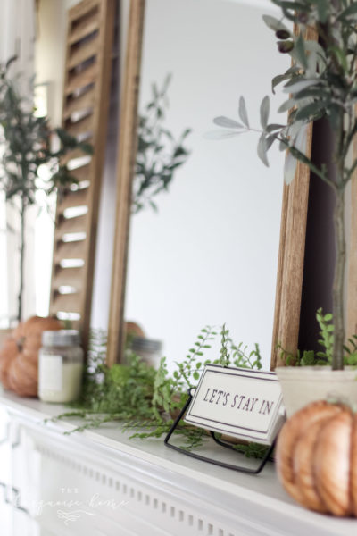 """Shutter and olive tree with """"let's stay home"""" sign and a wood grain pumpkin. Fall Mantel Decor #fallmantel #manteldecor #falldecor #homedecor"""