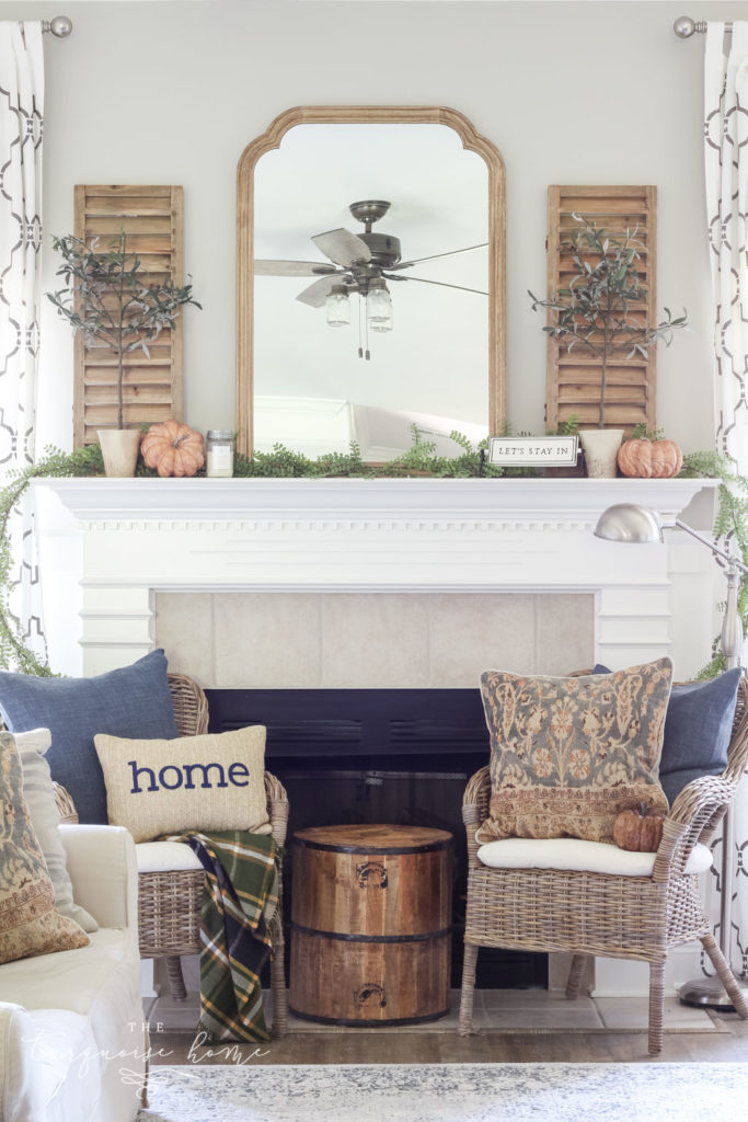 Beautiful neutral fall mantel with blues and browns and beautiful fall greenery.