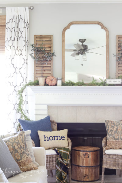 Beautiful neutral fall mantel with blues and browns and beautiful fall greenery. See all of the details and sources here: TheTurquoiseHome.com