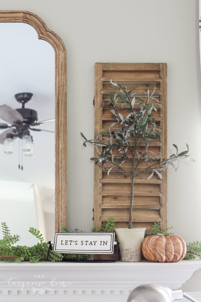 "Shutter and olive tree with ""let's stay home"" sign and a wood grain pumpkin. Fall Mantel Decor"