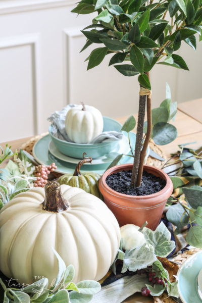 Pumpkins and Greenery Fall Tablescape with bay leaves in a pot and fall floral arrangement.