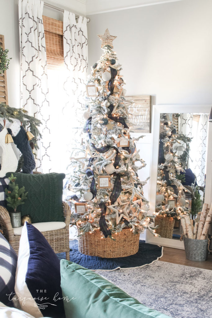 Gorgeous Flocked Christmas Tree with navy and green plaid ribbon and a basket tree collar.