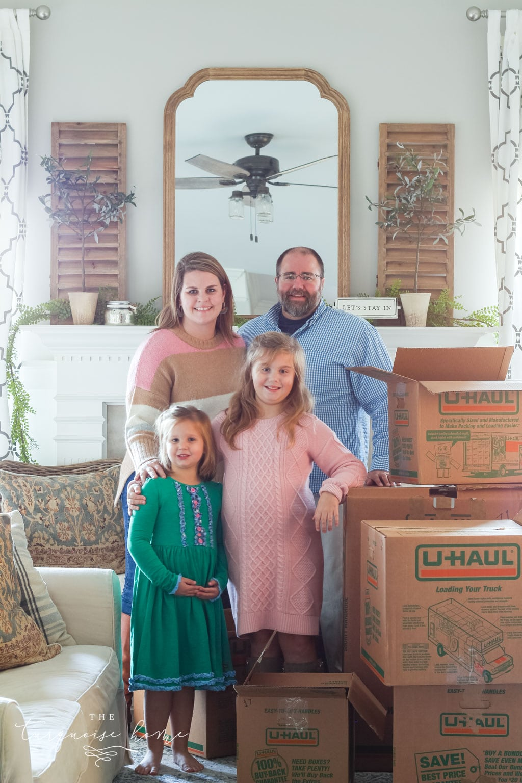 Family in front of fireplace with moving boxes