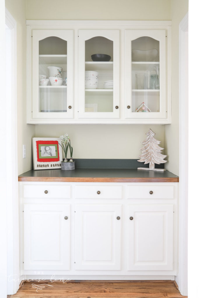 Butler's pantry with glass-front cabinets and hunter green countertops.