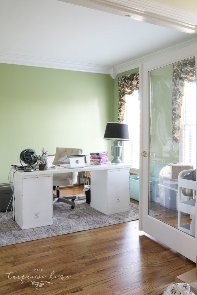 Feminine office with lime green walls and desk in the middle of the room.
