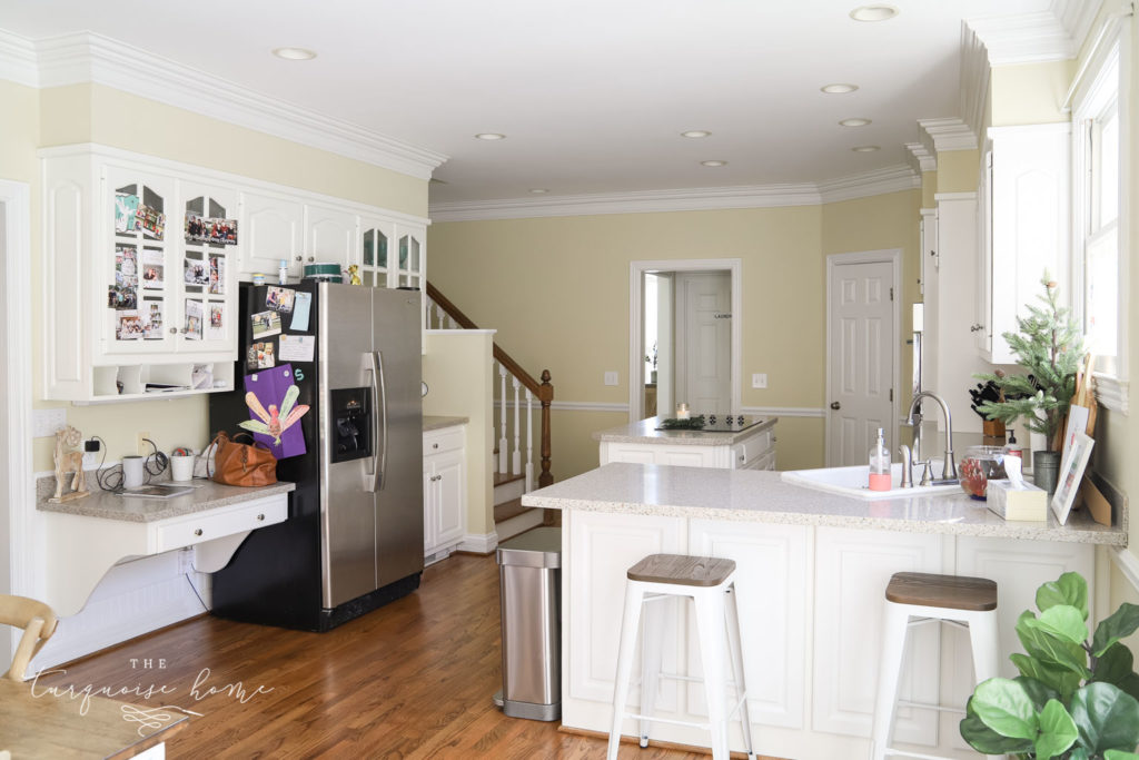 Large kitchen with white cabinets and working island.