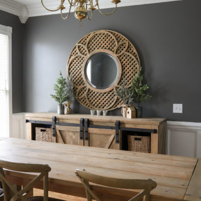 Kendall Charcoal dining room walls with wood buffet and large round mirror