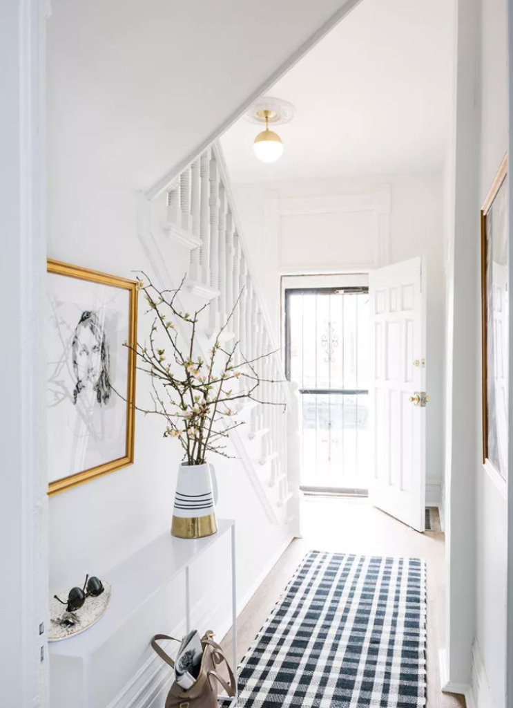white hallway with narrow white console table and blue checked runner rug