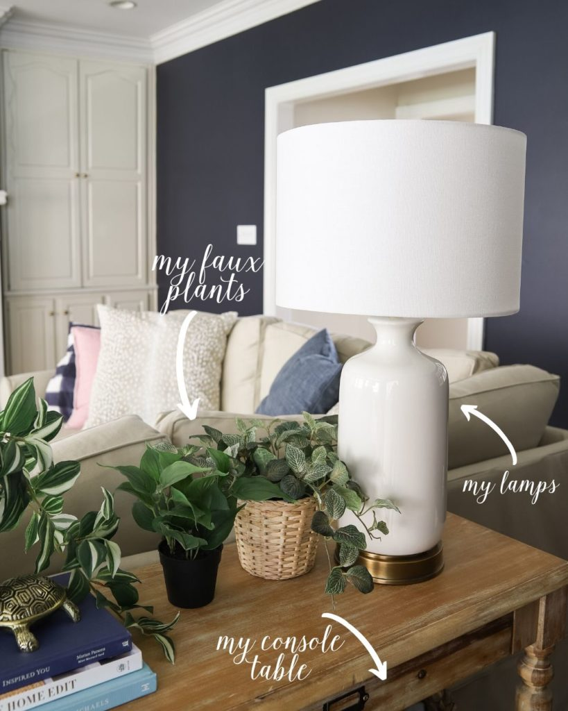 white lamps, faux plants and console table