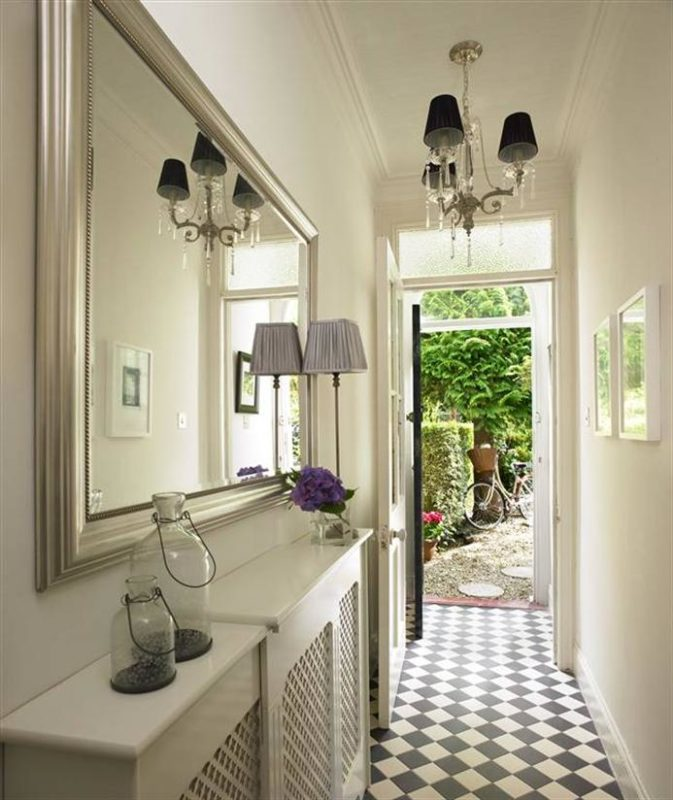 hallway with console table and hanging mirror to reflect the light