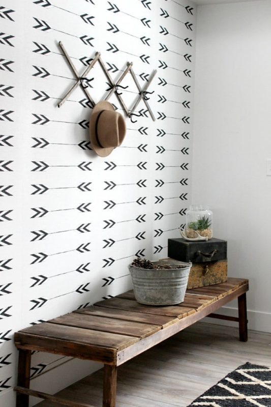 hallway with wooden bench and white wallpaper with black arrows