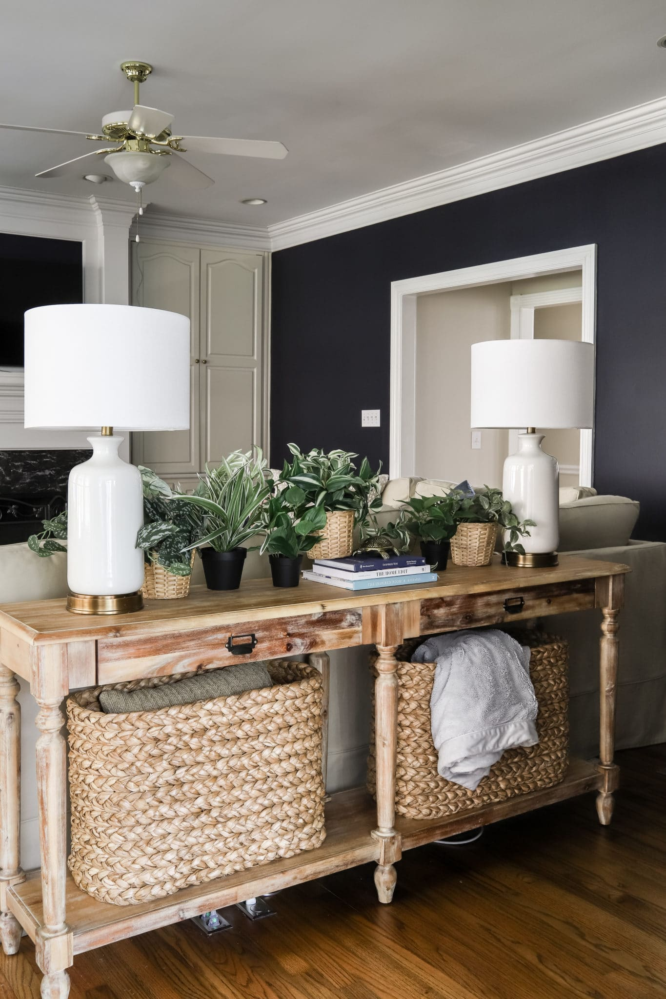 Everett Console Table with console table baskets, white lamps, faux plants and hale navy walls in living room