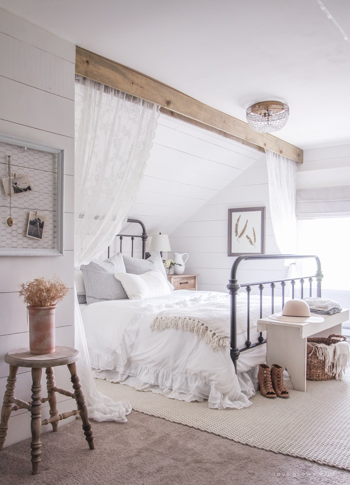 modern farmhouse bedroom with a bed, shiplap walls, and an area rug on the floor