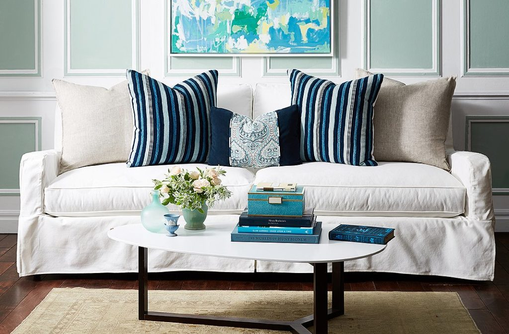 living room with cream sofa and dark blue throw pillows that bring in colors from all over the room