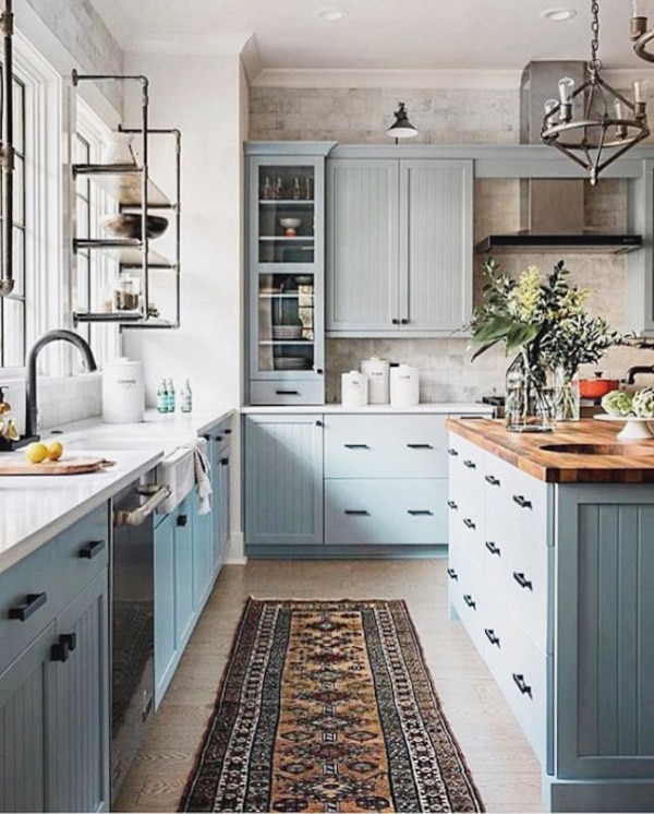 farmhouse kitchen with light blue cabinets, butcher block countertops and runner rug on the floor