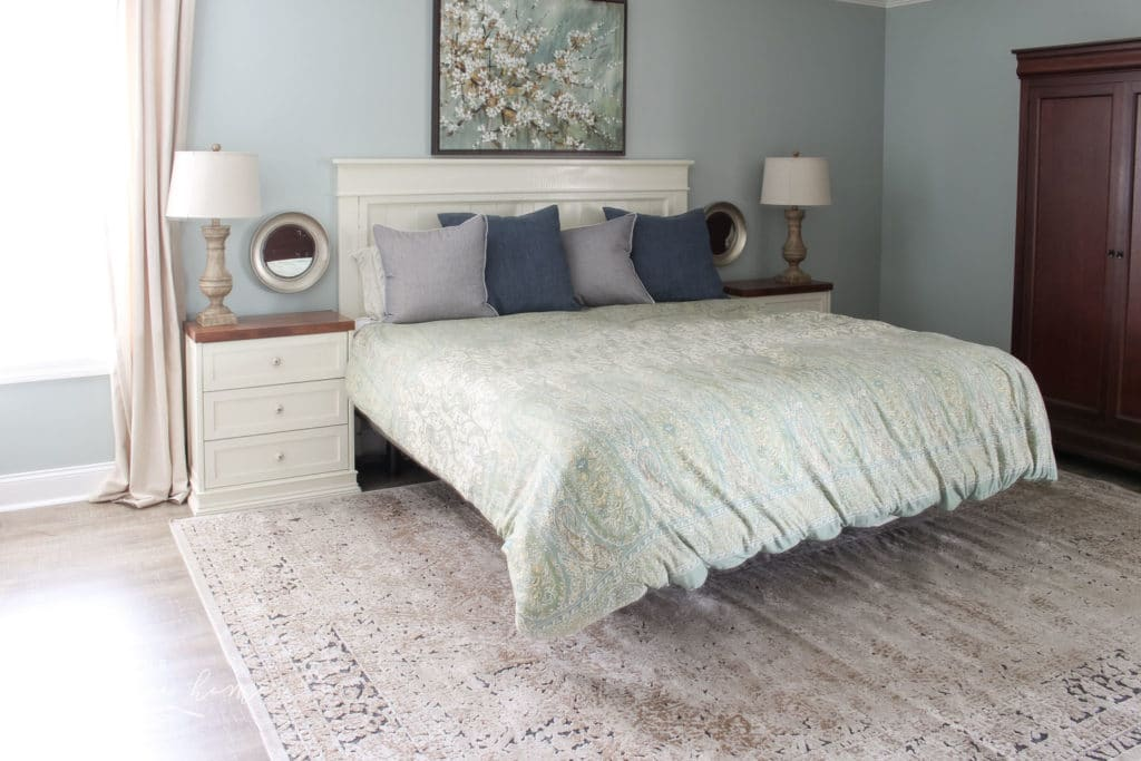 master bedroom refresh with throw pillows on the bed, a duvet cover, and an area rug under most of the bed