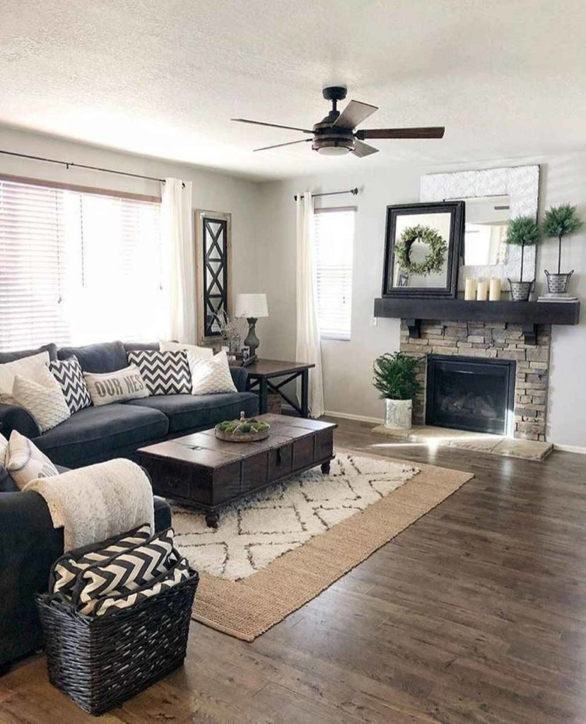 farmhouse style living room with couch in front of a window, a fireplace, and a coffee table