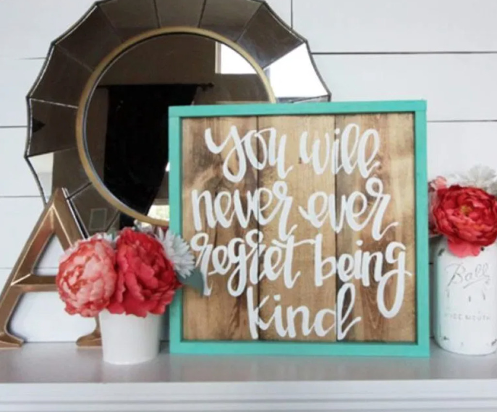 mirror, framed quote, flowers on a fireplace mantel