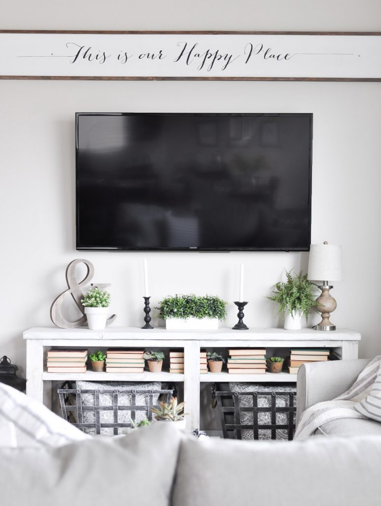 summer fireplace decor of greenery, candles, and a lamp that fit under a TV
