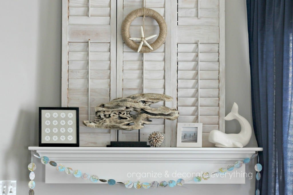 neutral beachy mantel decor with driftwood and framed sand dollars