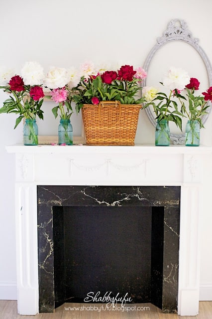 white fireplace with a basket of flowers and jars filled with flowers on the sides