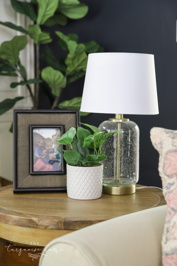 end table with lamp, frame and greenery