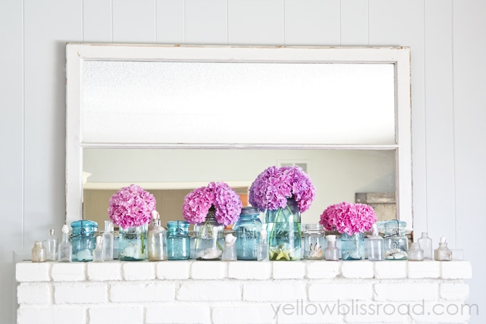 bright pink blooms and blue jars in front of a mirror on a mantel