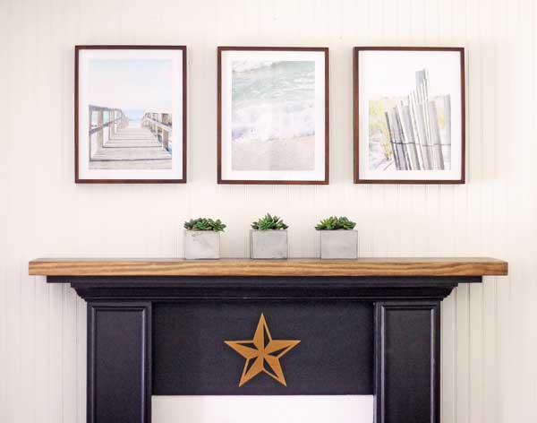 three framed beach image hanging over a mantel with three small potted plants