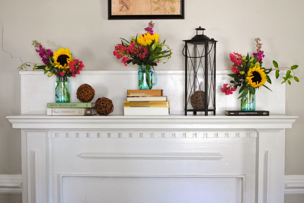 bright pops of color through flowers in mantel decor