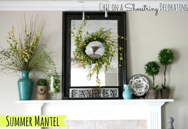 mantel decor with a wreath in front of a mirror, topiaries, and splashes of turquoise