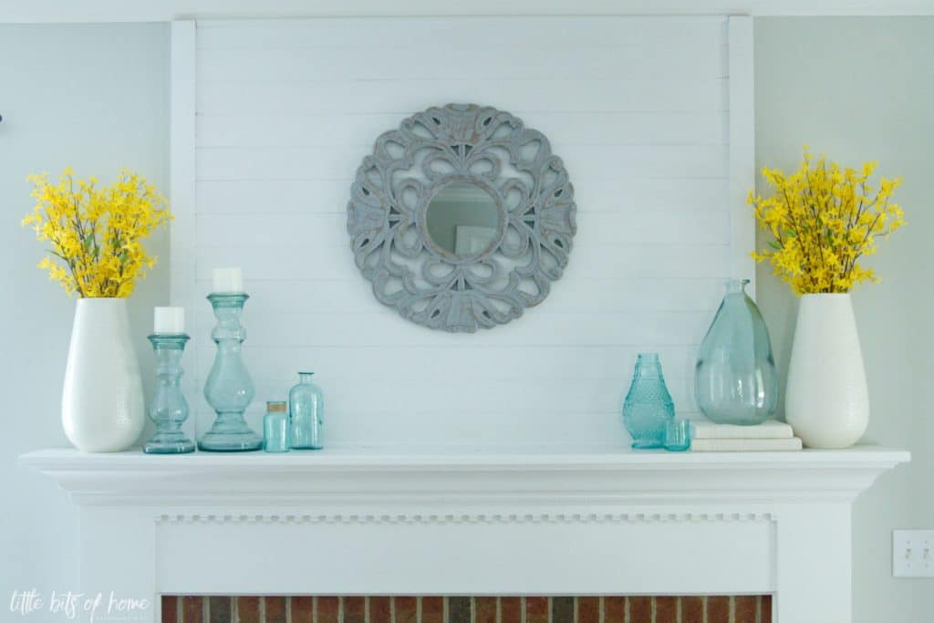 fireplace mantel with statement mirror, blue sea glass and yellow forsythia blooms