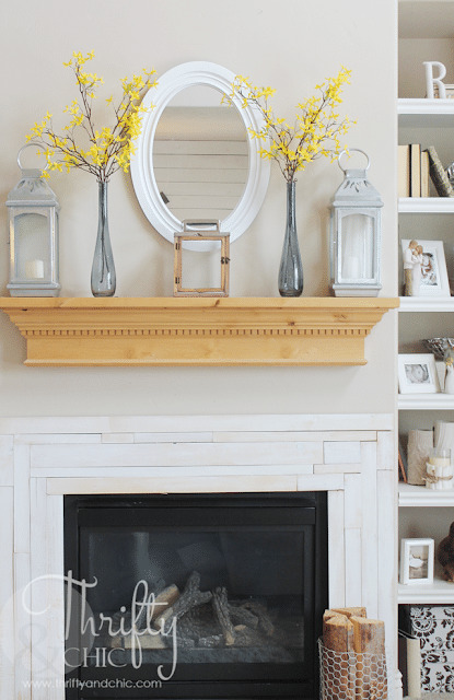 simple mantel decor consisting of three lanterns and two tall bottles with blooming branches