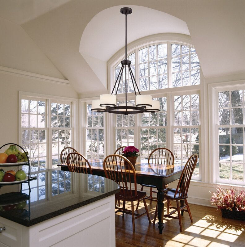 shaded wagon wheel chandelier hanging over an eat in kitchen table