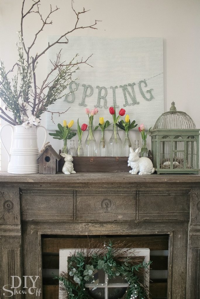 spring decor mantel with bunnies, bird cage, tulips and a spring sign